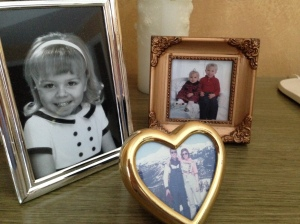 Three family photos on top of a dresser.