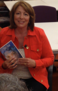 Marcia Coffey Turnquist holding her book, The God of Sno Cone Blue.