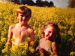 Yellow flowers surrounding Macklin and Amelia in a field.