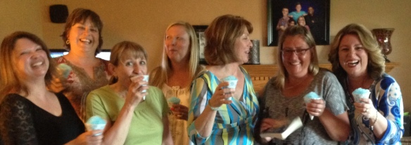 Book club members laughing with blue sno cones.